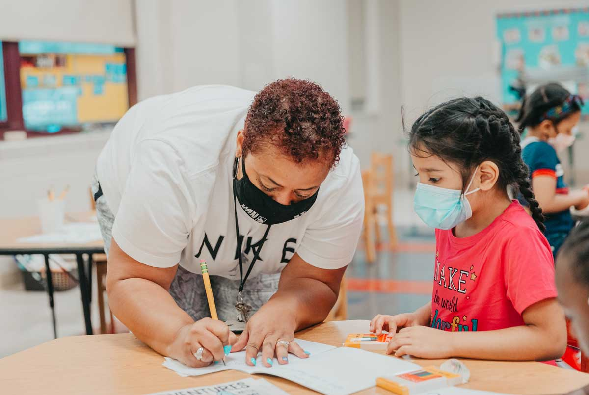 Claremont Academy teacher helping student in class