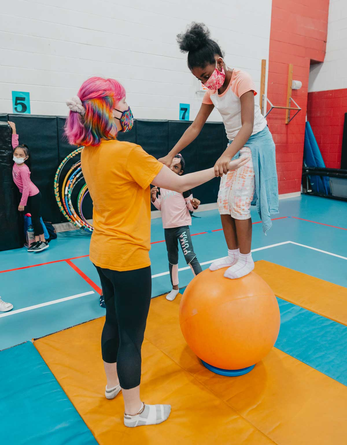 student standing on ball with help